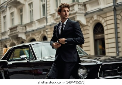 Young handsome man with black classic car wear black suit
