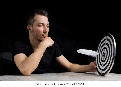 A young handsome man in black clothes sits at a table holding a dart board with a quill pen stuck in the center of the target on black background in a low key. Writing author goal achievement concept
