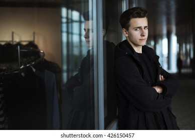 Young handsome man in black coat standing near shop with hands crossed. Outdoor shot