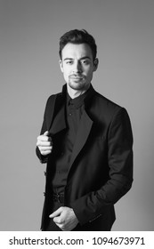 Young handsome man in a black suit, standing and seriously looking at the camera, against plain studio background