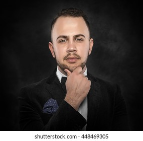 Young handsome man in black suit on dark background.