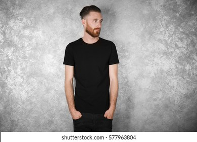 Young handsome man in black T-shirt on colour textured wall background