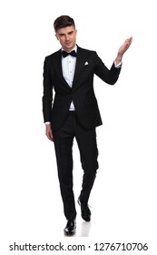 young handsome man in black tuxedo presents to side while standing on white background