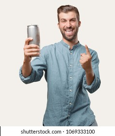 young handsome man, blue denim shirt, holding a beer pint, dancing or celebrating expression . person isolated against monochrome background