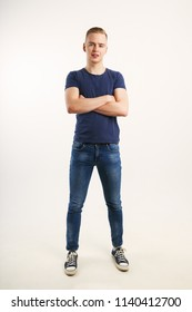 Young handsome man in blue shirt and jeans poses with crossed arms in white studio, full body