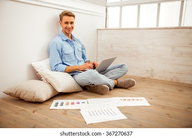 Young handsome man in the blue shirt and jeans, with a cup in hand, using laptop, sitting on cushions on the floor, next are graphics, sitting on the floor at home