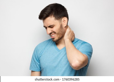 Young handsome man in blue tshirt, touching his neck because it hurts after long working hours, feeling exhausted and worried, isolated on gray background