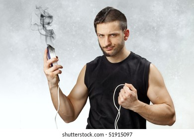 A young and handsome man with a broken and exploded clipper in his hand which left him half shaved and trimmed. The concept of do-it-yourself accidents and disappointment/frustration.
