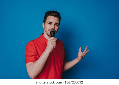 Young handsome man in casual clothes singing with microphone on blue background. He is looking at camera and gesticulating with hand. Human emotions and face expressions concept. Copy space in right