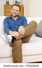 Young handsome man in casual denim wear comfortably sitting on white couch legs crossed, smiling and looking away