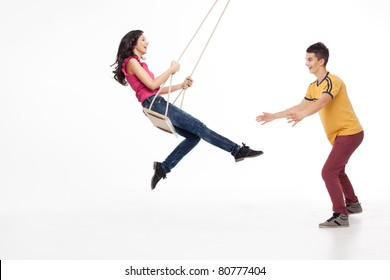 young handsome man catching his swinging girlfriend