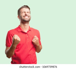 young handsome man celebrating a victory wearing a red polo shirt . person isolated against monochrome background