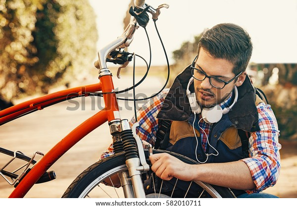 Young handsome man is checking brake on his bike.