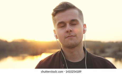 Young handsome man closed eyes listens to music on beach during sunset.