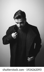 Young handsome man in coat with beard and piercings portrait black and white poster. Guy model posing in outerwear. Successful young man with black hair in dark clothes