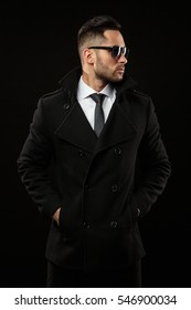 Young handsome man in a coat and sunglasses - studio male portrait