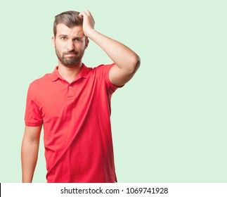 young handsome man confused wearing  red polo shirt . person isolated against monochrome background