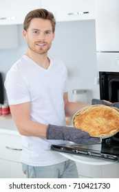 young handsome man cooking pie