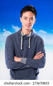 Young handsome man with crossed arms on the Sea background