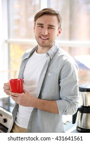 Young handsome man with cup of coffee in the kitchen