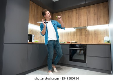 young handsome man dancing while cooking in the kitchen.