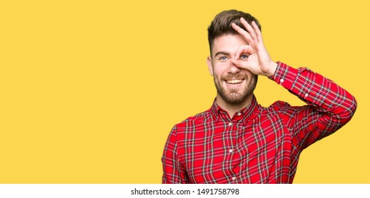 Young handsome man doing ok gesture with hand smiling, eye looking through fingers with happy face.