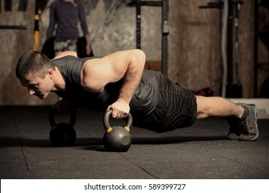 Young handsome man doing push-ups in gym