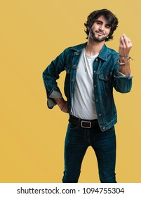 Young handsome man doing a typical italian gesture, smiling and looking straight ahead, symbol or expression with hand, very natural