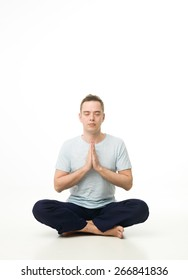 young handsome man doing yoga and meditating on white background. copy space available