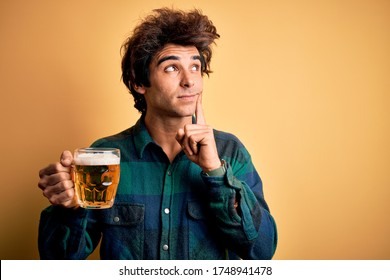 Young handsome man drinking jar of beer standing over isolated yellow background serious face thinking about question, very confused idea