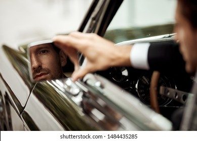 Young handsome man driving a car and looking at mirror