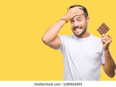 Young handsome man eating chocolate bar over isolated background stressed with hand on head, shocked with shame and surprise face, angry and frustrated. Fear and upset for mistake.