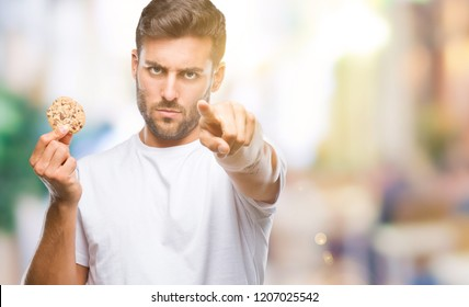 Young handsome man eating chocolate chips cookie over isolated background pointing with finger to the camera and to you, hand sign, positive and confident gesture from the front