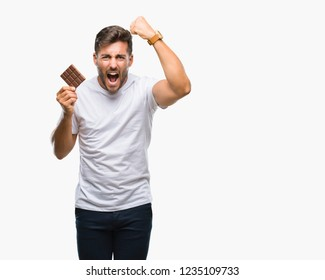 Young handsome man eating chocolate bar over isolated background annoyed and frustrated shouting with anger, crazy and yelling with raised hand, anger concept