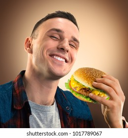 Young handsome man eating a hamburger. Portrait of a happy guy with a hamburger in his hands. Advertising fast food. Tasty cheeseburger.