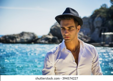 d4810e8a871c8d Young handsome man in elegant white shirt and black fedora hat, on beach  while looking