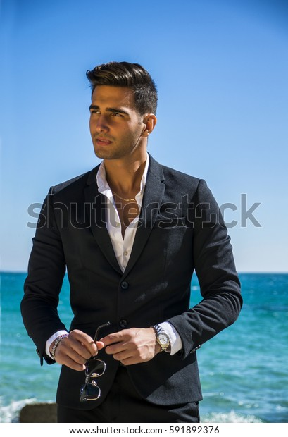 Young handsome man in elegant white shirt and business suit, on beach while looking away. Sea waves on background