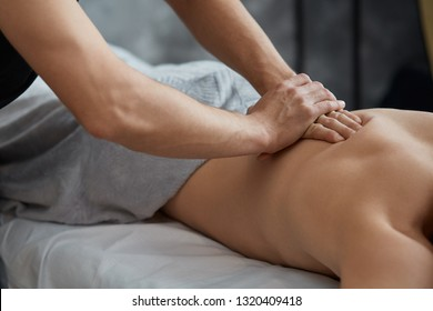 Young handsome man enjoying a back massage. Professional massage therapist is treating a male patient in apartment. Relaxation, beauty, body and face treatment concept. Home massage.