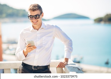 Young handsome man enjoying stay at luxury resort hotel with panoramic view on the sea.Smiling business man using his smartphone options at a earned tropical vacation.Business traveling.Outsourcing