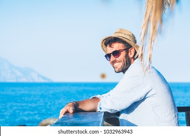 Young handsome man enjoying the view at the beach bar