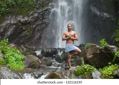 Young handsome man enjoying  yoga at waterfall in the tropics