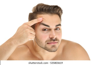 Young handsome man examining his face on white background