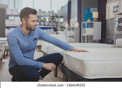 Young handsome man examining orthopedic mattress on sale at furniture store, copy space. Attractive male customer buying new bed at homeware supermarket. Consumerism, home concept