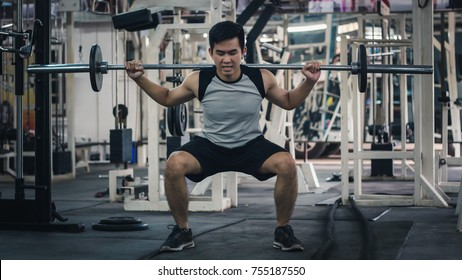 Young handsome man exercising with a barbell squat in a gym