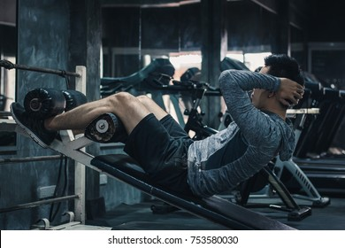 Young handsome man exercising sit up in a gym