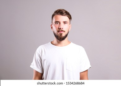 Young handsome man with facial hair posing over gray wall with a lot of copy space for text. Portrait of confident bearded male, wearing blank white oversized t-shirt. Isolated, background.