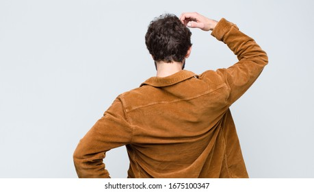 young handsome man feeling clueless and confused, thinking a solution, with hand on hip and other on head, rear view against flat wall