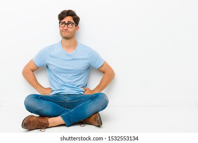 young handsome man feeling confused or full or doubts and questions, wondering, with hands on hips, rear view sitting on the floor