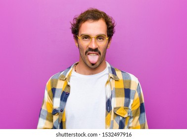 young handsome man feeling disgusted and irritated, sticking tongue out, disliking something nasty and yucky against purple wall