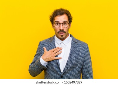 young handsome man feeling shocked, astonished and surprised, with hand on chest and open mouth, saying who, me? against orange wall